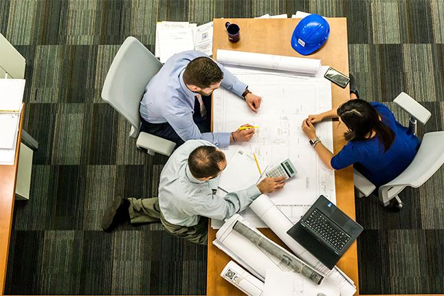 Three engineers - two men and a woman sitting on a table and working on a plan