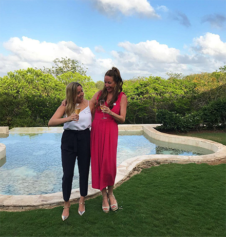 Two women cheering with a glass of champagne by a swimming pool