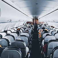 Plane seats with people from the back of a plane